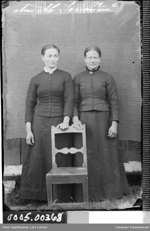 Portrett av to unge kvinner iført todelte drakter i helfigur.