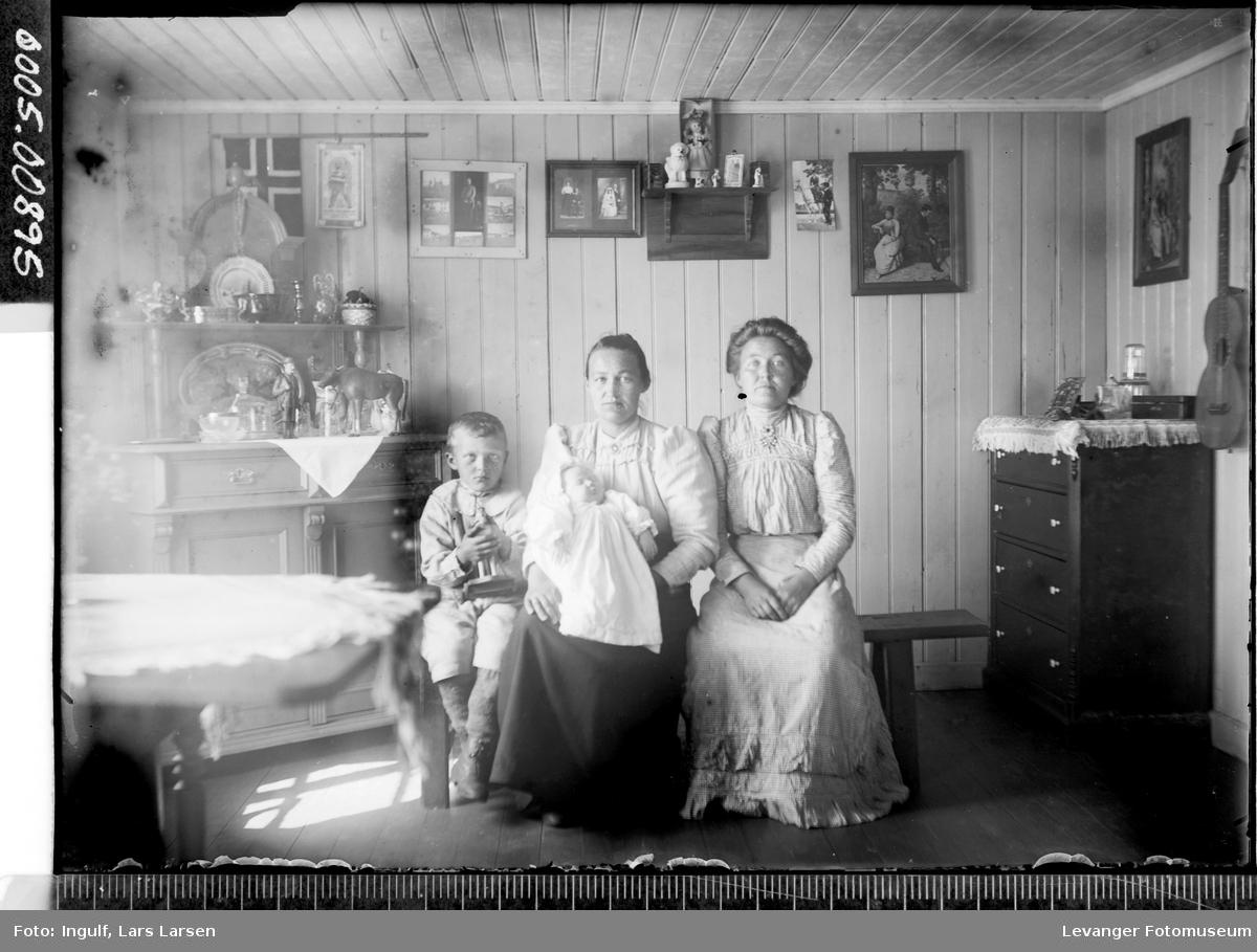 Gruppebilde av to kvinner, en gutt og et spedbarn.