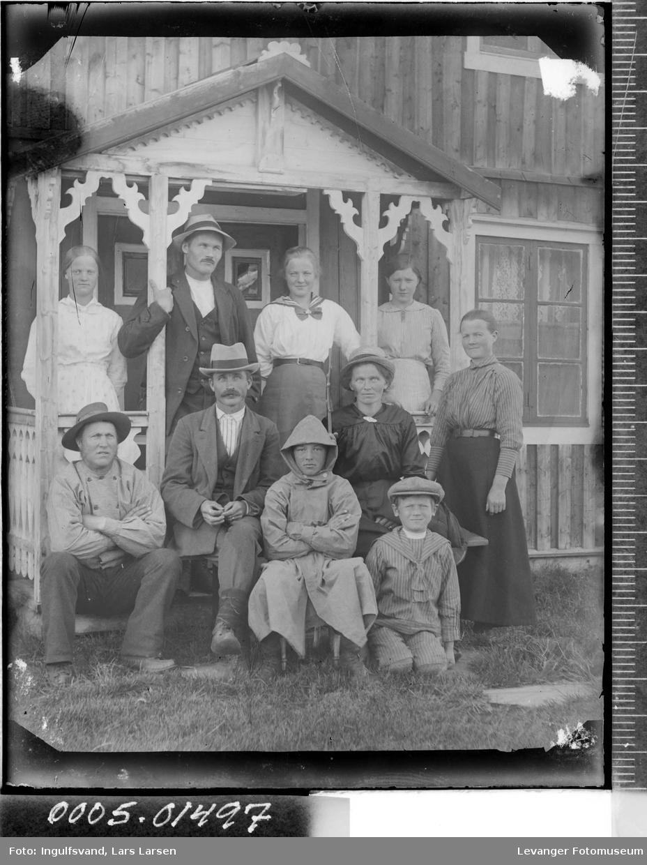 Gruppebilde av tre menn, fem kvinner og to gutter foran et inngangsparti.