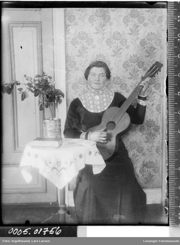Portrett av en kvinne som spiller gitar.