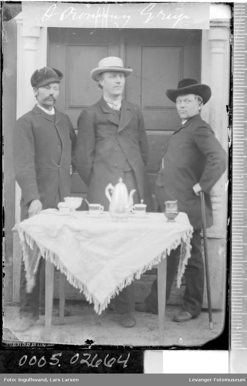 Gruppebilde av tre menn ved et bord foran et inngangsparti.
