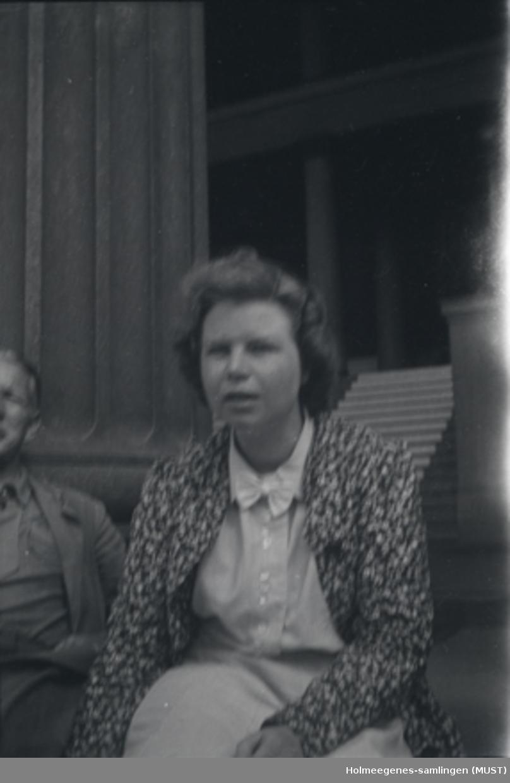 En kvinne, halvnært, sittende på trappene til Universitetet i Oslo.