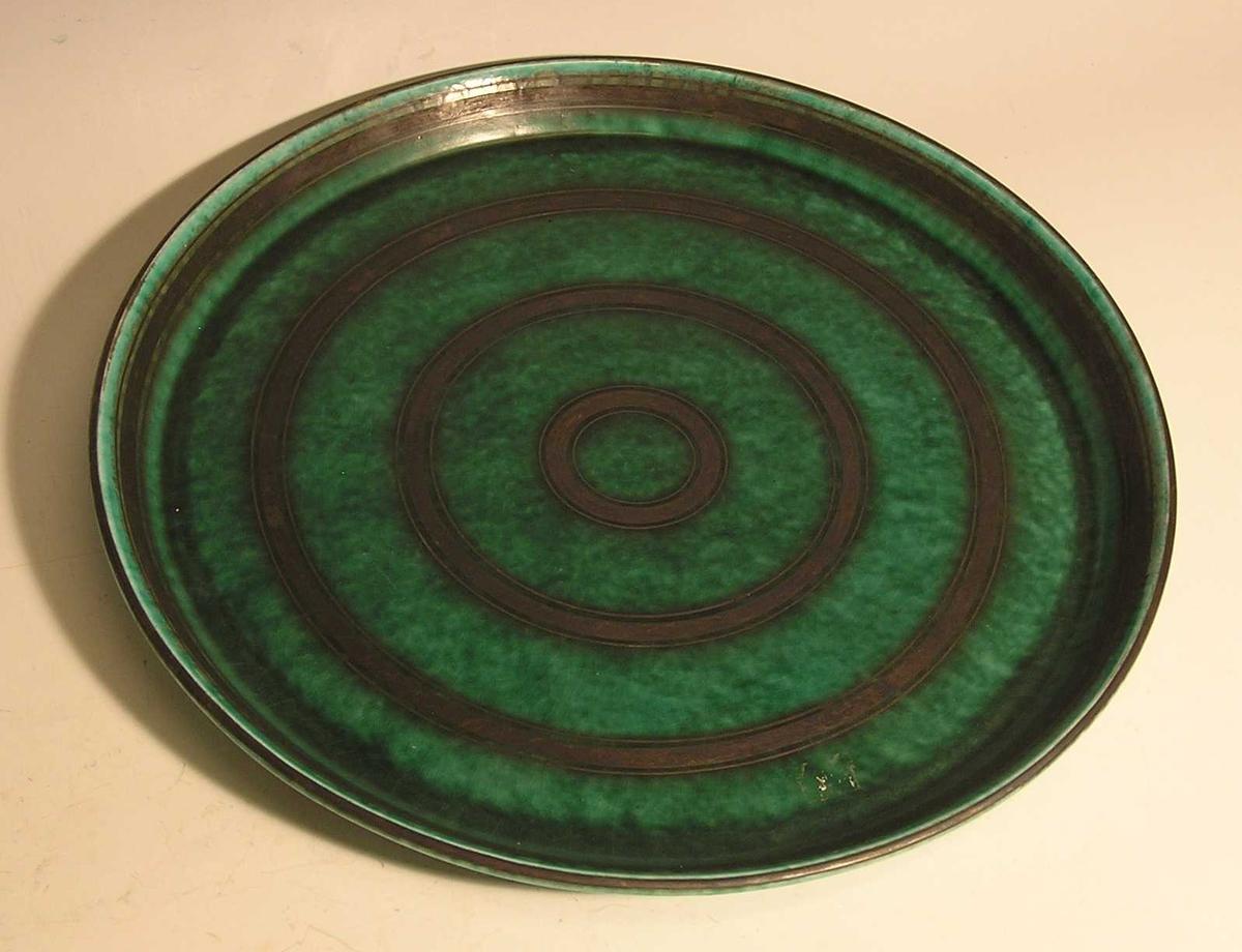Sølv innlagt i keramikk. Sølvringer har bladmønster . Små og større ringer danner mønsterborder.