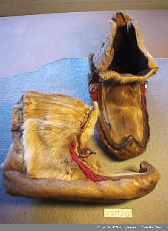 Et par skaller, sydd av to ulike typer skinn. Sålene er slitt. Lite stykke rødt klede foran og to skinnhemper hvor skallebåndet skal festes.
