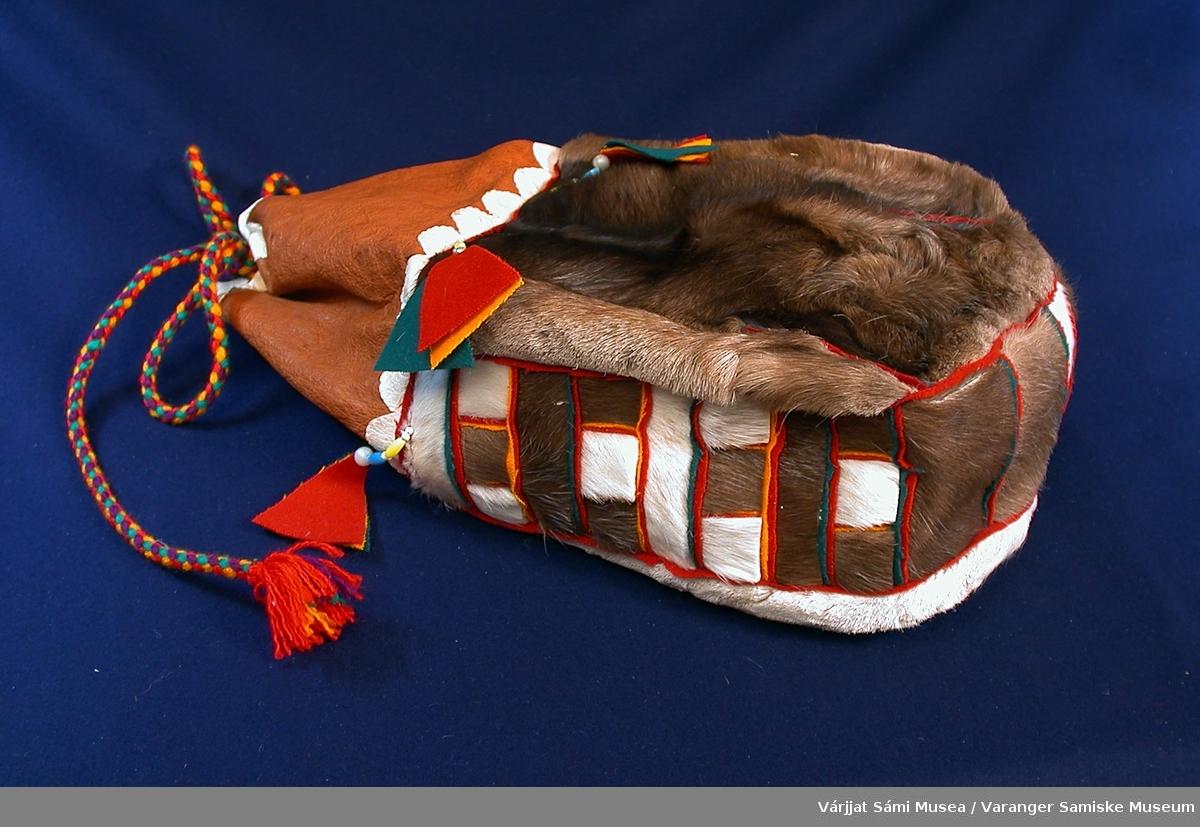 650-1: Sekk av reinskinn (med hår) og klede. Den har form som en stor kaffepose, med åpning og surring oppe. 3/4 av front og bakstykke er av reinskinn. Den øverste (mot åpningen) 1/4 og bunn og sider er av klede i ulike brunfarger, hvitt og rødt. Sekken er pyntet med trekantdusker av klede i rødt, blått og gult i overgangen meloom skinn og klede. duskene henger fast i en kort perletredd snor. Perlene er gule, lyseblå og hvite. Sekken trekkes igjen med tvunnede ullsnorer i gult, rødt og blått. Lengd/høyde ca. 35 cm.   650-2:Flettet herrebelte av ull, i fargene rød, mørkeblå og hvit. Beltet ender i en dusk i hver ende.