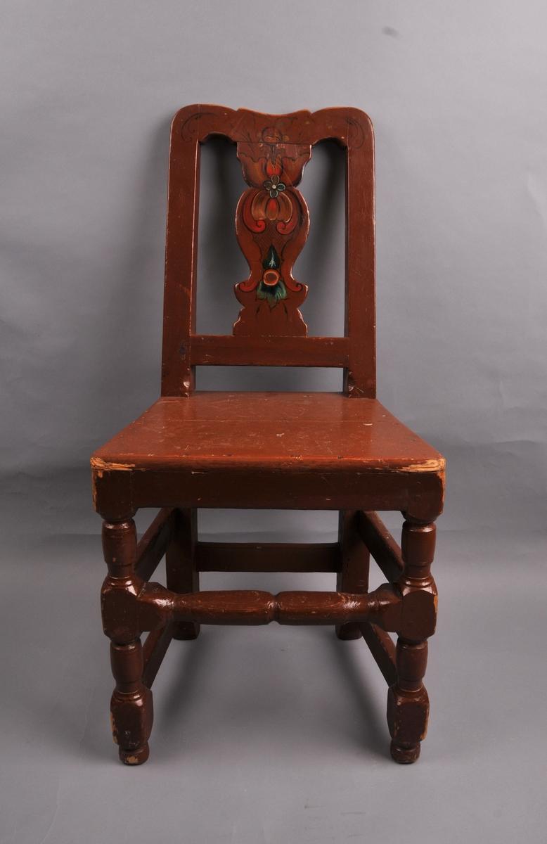 Brunmåla stol med rosemåling på rygglene.