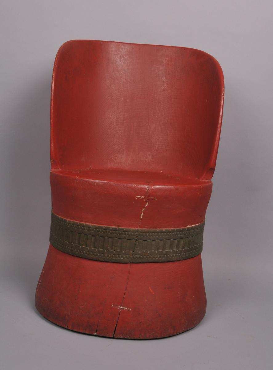 Kubbestol med utskore band i geometriske mønster. Uthola, innfelt sete. Ein utskoren bord langs stolryggen på baksida. Måla i seinare tid.