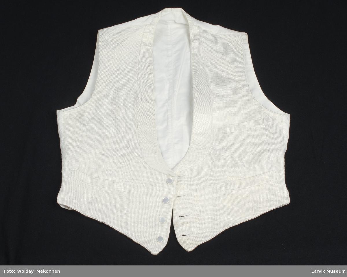 Form: forstykkene av silke,rygg og fór av lasting, 4 løsknapper av perlemor med metallstifter på vrangen, 1 tøyknapp på spensel i ryggen, nedsydd sjal- krage på forstykkene,3 skrålommer