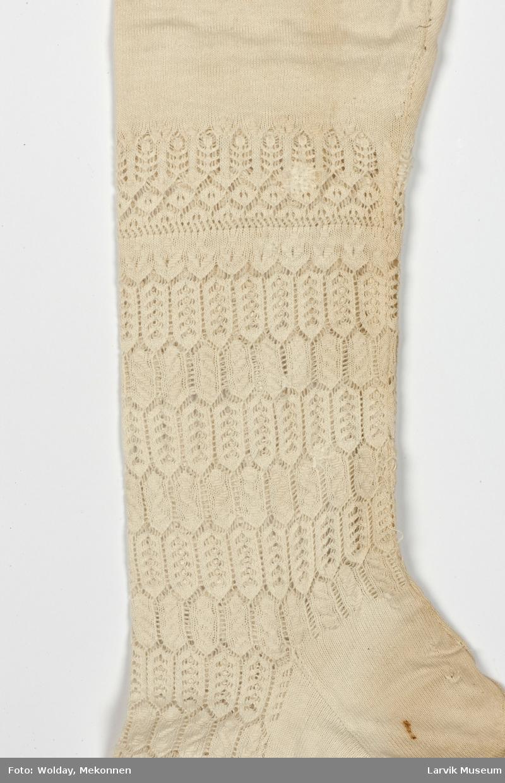 Form: Maskinstrikket med hullmønster fra vrist og et stykke opp over ankel. Øverst to smale røde streiper i jarekant. Hempe på innsiden