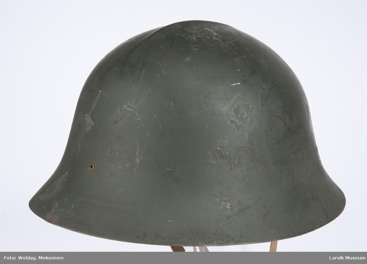 Form: Metall hjelm, m/polstring inni av skinn og bomullstoff. Rem for feste under haken.