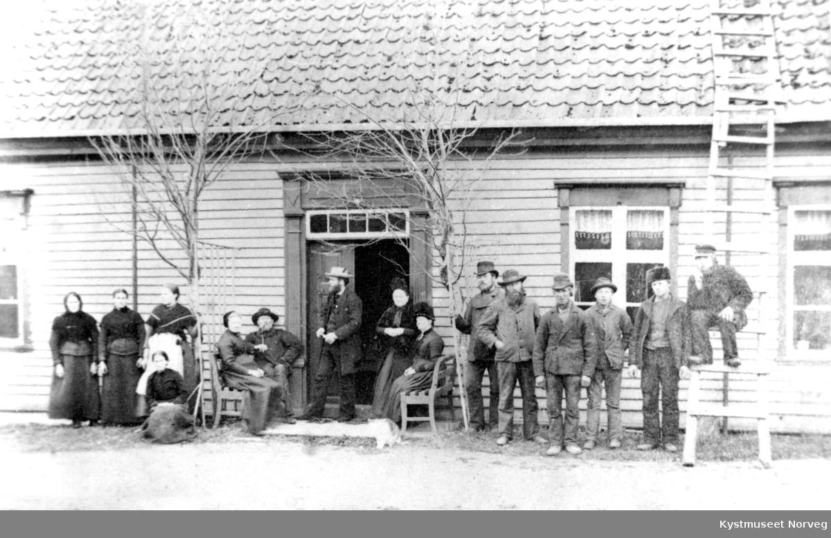 I døren på Prestegården står Prest Nordtømme og Prestefruen sammen med ukjente