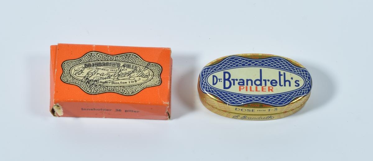 """a) er en oval pilleeske i metall, b) er en liten rektangulær pappeske til samme type piller fra samme fabrikant. Del b) kan være emballasjen til del a), selv om de er omtrent like store. Del a) er gullfarget med påtrykt """"etiketter"""" over og under på esken, disse er i hvitt, blått og rødt. Esken er tom. Del b) er oransje med tekst/trykk på alle de seks sidene. På over- og undersiden av esken er det påtrykt """"etiketter"""" i fargene lys gul og svart."""