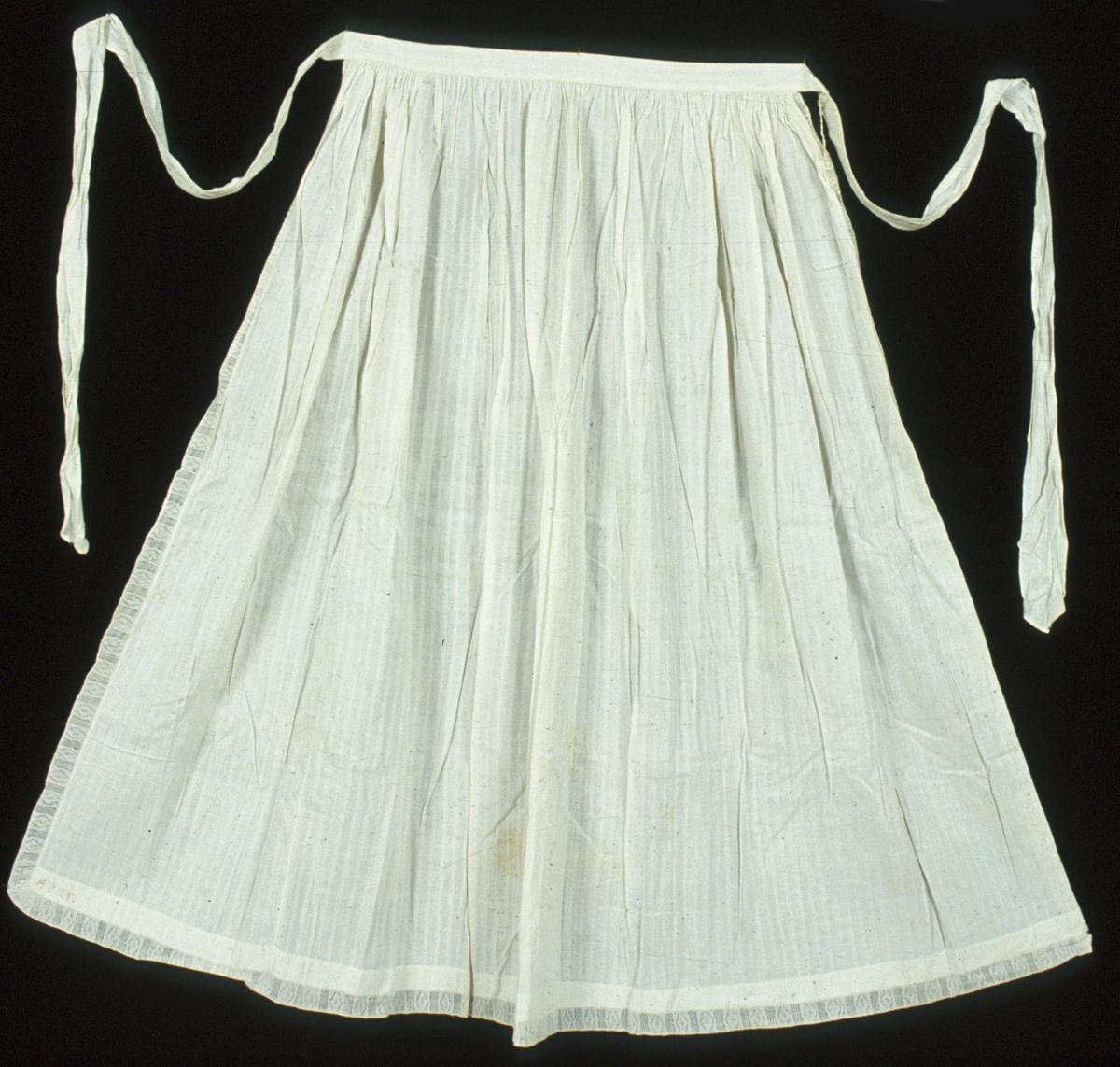 """Vitt förkläde i bomull. Tyget är mönstervävt med ränder vitt-i-vitt i kypert och ?-bindning. Längs sidorna och nedtill är förklädet dekorerat med en påsydd 22 mm bred, vävd vit spets. Förklädet är rynkat mot linningen, upptill är bredden 445 mm. Linningen fortsätter utanför förklädet i 150 mm på var sida och utgör början av knytbanden. Knytbanden är sydda i samma tyg och är ca 1230 mm långa och i den förlängda delen 70 mm breda. Förklädet är sytt av två olika stora stycken med en söm 260 mm innanför ena långsidan. Fållarna innanför spetsen är mycket smala i sidorna och 25 mm bred nedtill. Både hand- och maskinsydda sömmar. Broderad märkning i korsstygn i rött: """"N 25 B"""" nedtill på fållens insida."""