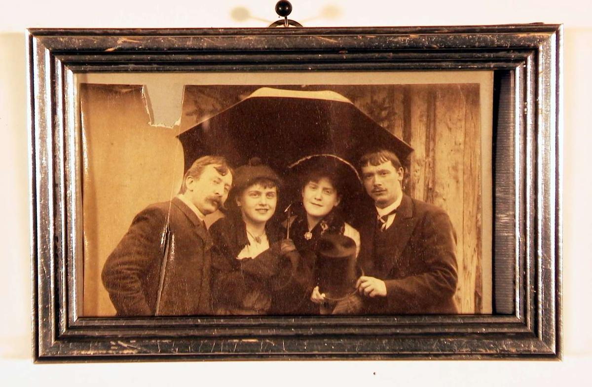 Fotografi av to unge damer i midten og en herre på hver side, samlet under en paraply.