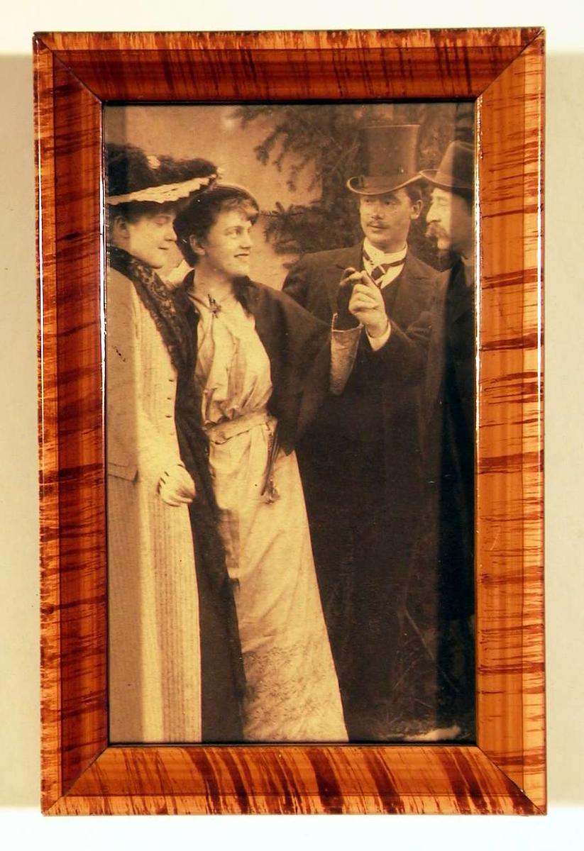 Fotografi av to unge damer til venstre og to unge herrer til høyre i bilde; den en herre hilser med tommeltott mot tommeltott med den en dame, de ser på hverandre.