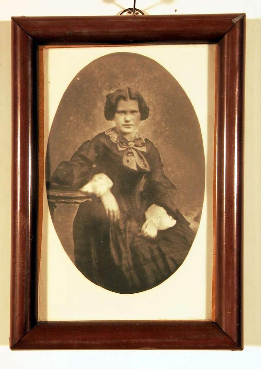 Portrettfotografi av en ung dame sittende med høyre arm hvilende på pidestalbord. Hun er ikledd en mørk kjole med snøreliv (korsett), store hvite kniplingsmansjetter og en stor sløyfe i halsen. Frisyren er oppsatt med midtskill.