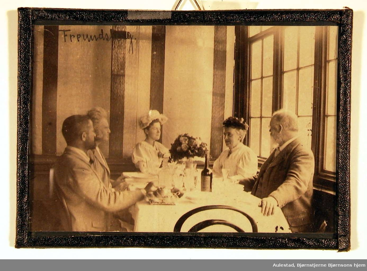 Fotografi fra spisesal; ved bordet sitter to damer og tre herrer; de ser på hverandre.