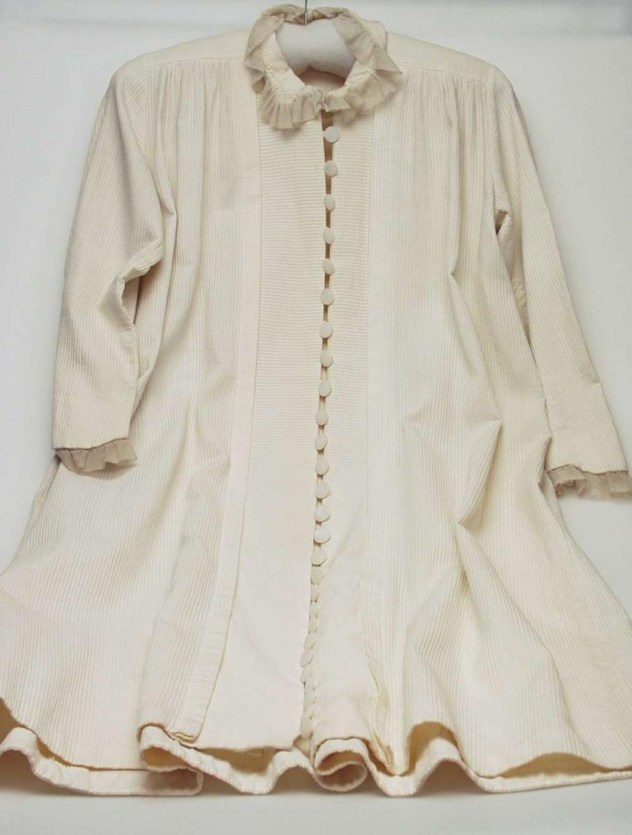 Lang hvit frontknappet kjole i bomullspicquet med stripet struktur. Kjolen har 28 perlemorknapper som lukkes med hempe. To skrådde sømmer/kiler under hvert erme. Skulderstykket av tøy på tvers. Forstykket er rynket inn i skulderstykket. Kjolen er åpen fra halsen og ned. 10 cm bredt, tverrstripete parti sydd til forstykket med en mot midten brettet 1,5 cm dyp fold danner frontpartiet. 4,5 cm belegg i oppbrett nederst. Stående linning, 44x6cm, der baksiden er belagt med to-skafts bomullslerret og kantet med dobbel rynket tyllkant. Smalt to-søms erme med høy topp og buet linje ned over håndbaken, belagt og kantet med 3 cm bred, dobbeltlagt rynket tyll/bobinette. Alle belegg og skonninger av to-skafts bomullstøy.