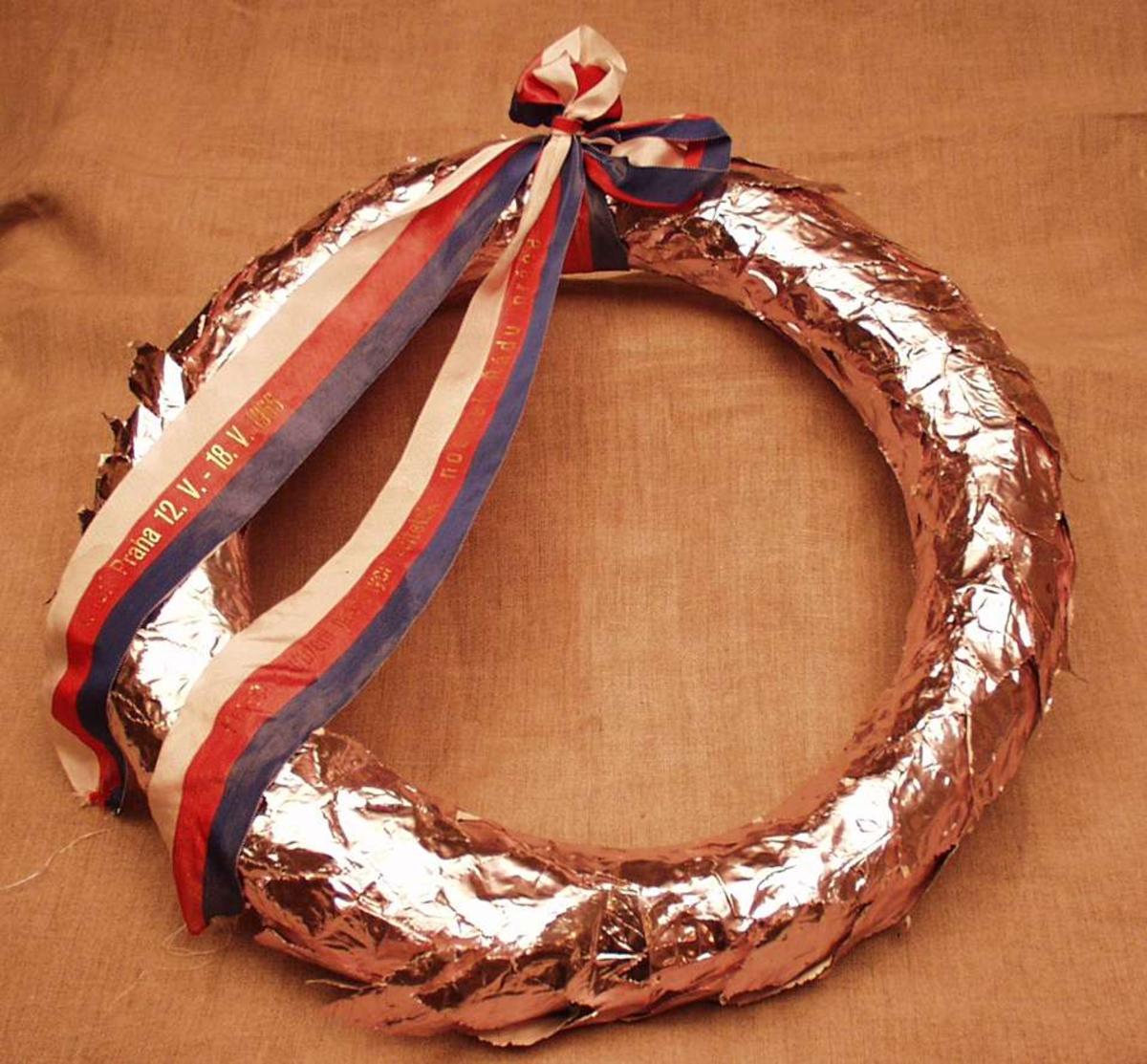 Krans i aluminiumsfolie, pyntet med bånd i rødt, hvitt og blått.