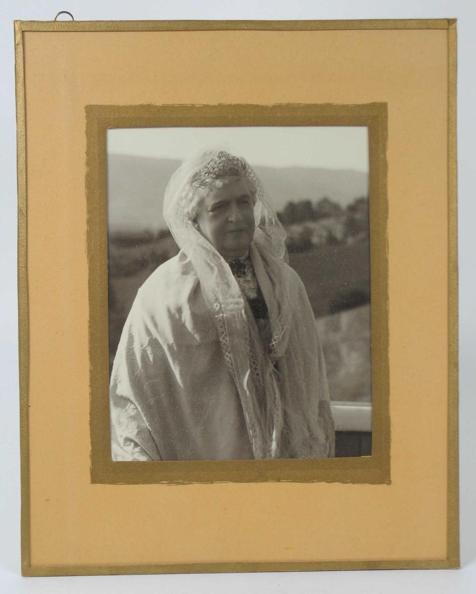 Eldre kvinne i hvitt fotografert på veranda.