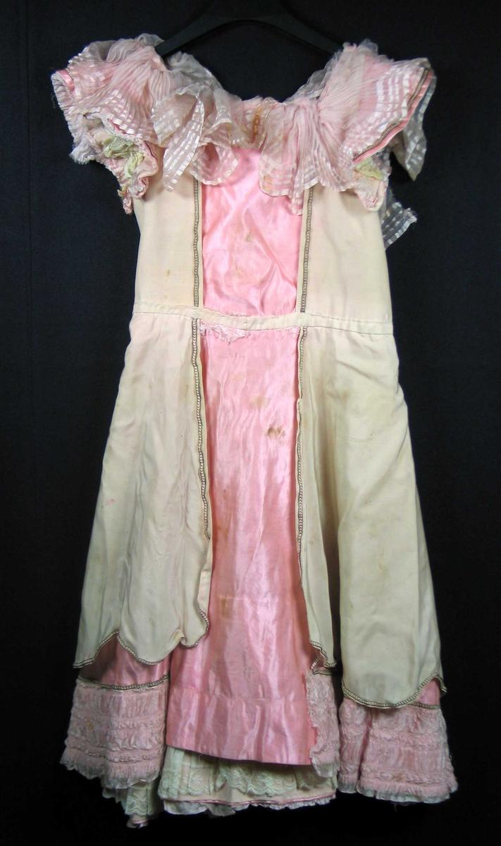 Kjole avdelt i livet. Skjørtet er halvsirkelskåret med to smale bredder midt bak, fransksøm. Livstykke med sidesøm og hektelukking i ryggen. Vid halsutringning, fôret med samme tøy. Glatt, vidt kapperme. Alt i rosa silkesateng. Under skjørtekant 18 cm stivet bomullskappe med blondekant. Under ermet stivet, foldelagt bomullskappe med blondekant. Nederst på skjørtet, 12 cm bred rosa natursilke, plisért, rynket rysjekant. Over og under ermkant 3 cm bred tilsvarende rysjekant. Utenfor halsskjæring 12 cm kant, innenfor 8 cm cm kant av plisért, stripete rosa natursilkerysj. Beige silkekasakk kantet med metallbånd dekker kjolen bortsett fra et åpent frontparti i hals 13 cm, i livet 11 cm og 13 cm opp fra nederkant ca 26 cm. Kasakken har store tunger nederst. Metallbånd på ermet, som markering for kasakkåpningen på rosa satengskjørt og langs rysjekant på skjørt. Omsøm med tråkling i livet. Rysjen i halsen er meget defekt. Hekter og trådmeller i ryggen delvis borte, avsprettet.
