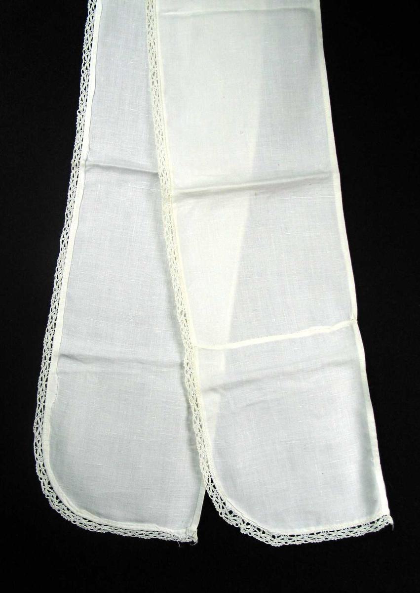Hvit løper i lin med påsydd blonde i forkant. Løperen har avrundede hjørner og en innskjøtt lengde på 18 cm i ene enden.