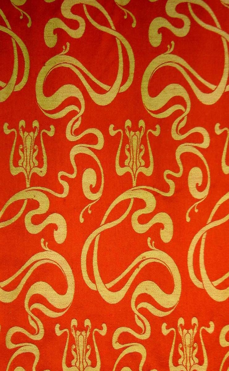 En rull med jacquardvevet ulldamask. Bunnfargen er rødoransje med organisk slyngete stilker/grener i grønt spredt utover flaten. Grunnbinding sateng. Renningssateng i rød bunn, innslagsateng i grønt mønster. En rapport: H:64 cm, Br 20,5 cm.