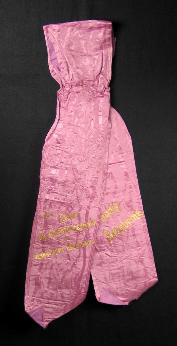 Begravelsessløyfe i lilla silke med innvevd mønster.