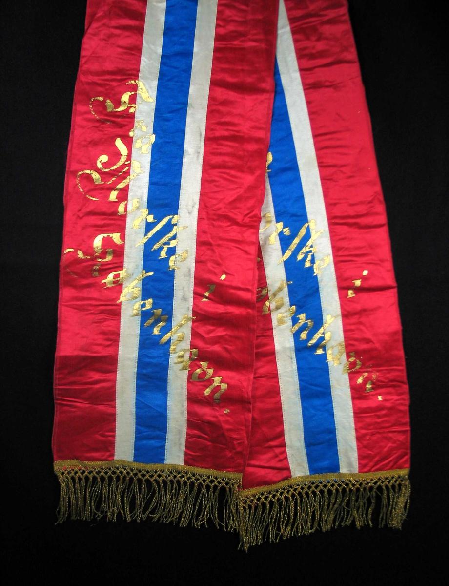 Begravelsessløyfe i rød, hvit og blå silke med frynser og tekst i gull.