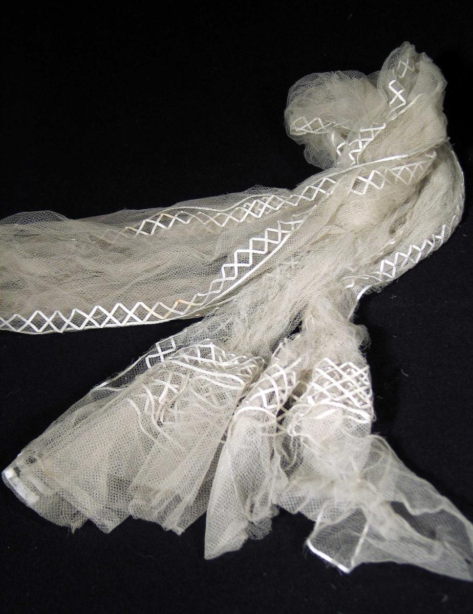 Hvitt slør av tyll med påsydde silkebånd i sikksakk-mønster/lissedekor. 9 cm dobbel tyll i endene. Borden er 3,5 cm bred. De 2 mm brede silkebåndene der tredd gjennom tyllen. Utenom en rett linje av en lisse som kanter sikksakkborden.