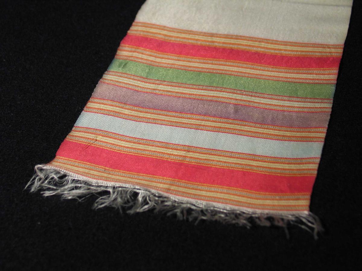 Bånd i natursilke med flerfargede striper i endene. Hvite frynser ytterst dannes av renningen. Vevbredde 14 cm. Innslaget glir ut. Beingult/hvitt midtparti.