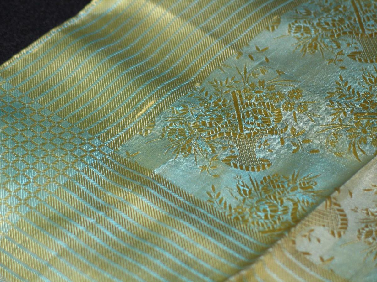 Jacquardvevd tørkle i natursilke. Det er gult og turkis og har motiv i form av blomsterkurver. Striper langs kanten og rutemønster i endene. Jare i to sider viser vevbredden, 53 cm. De øvrige to sider har smal maskinsydd fald.
