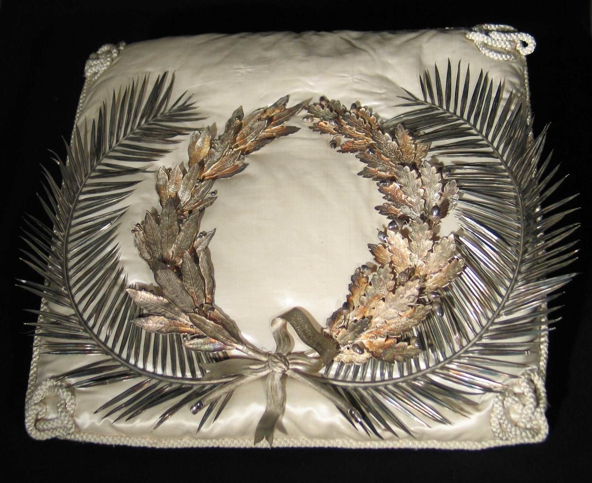 Dobbelkrans i sølv med palmekrans ytterst og laurbær og eikeløv innerst. Sløyfe nederst. Kransen er sydd ned på en hvit silkepute kantet med snorer og knuter i hjørnene. Kransen har et hvitt melkeaktig utseende, som sølv får som ikke er pusset og polert etter at det er glødet og dyppet i syre.(Oppkok av svovelsyre og vann.)