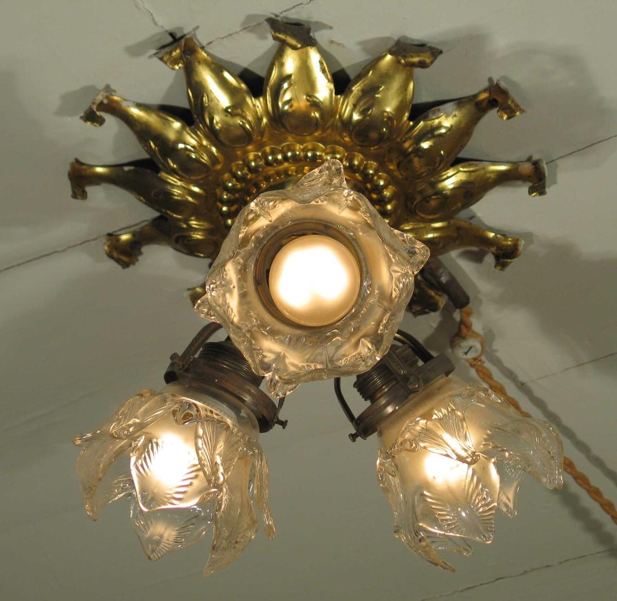 Taklampe i messing med tolvfingret rosett i taket. Den har tre lysarmer med dobbel bladformet glasskjerm.