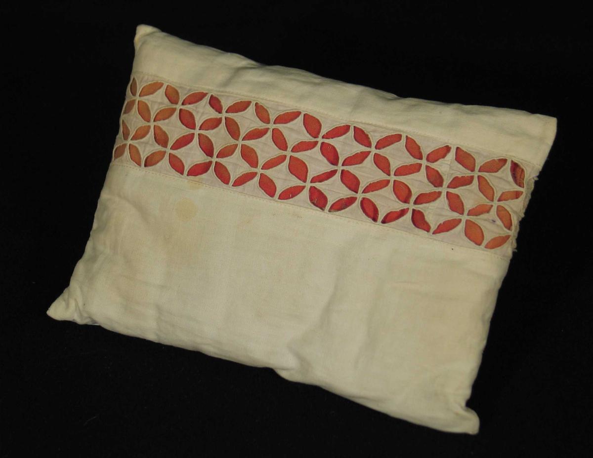 Hvit pute i tynt bomullsstoff til dokkeseng. Den har brodert mellomverk med rødt stoff under.