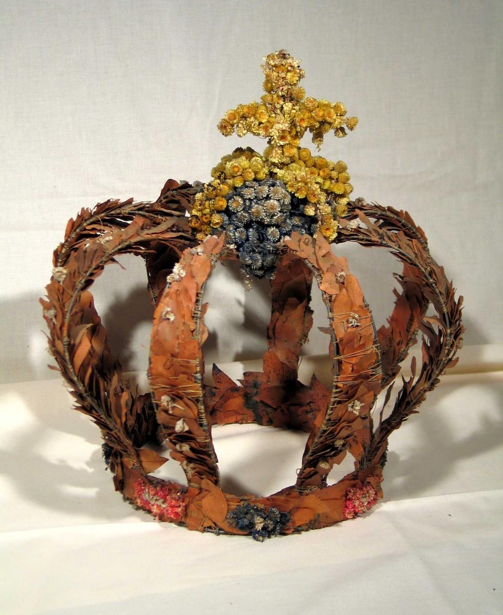 Krone bundet av laurbær med kors på toppen laget av tørkede blomster.