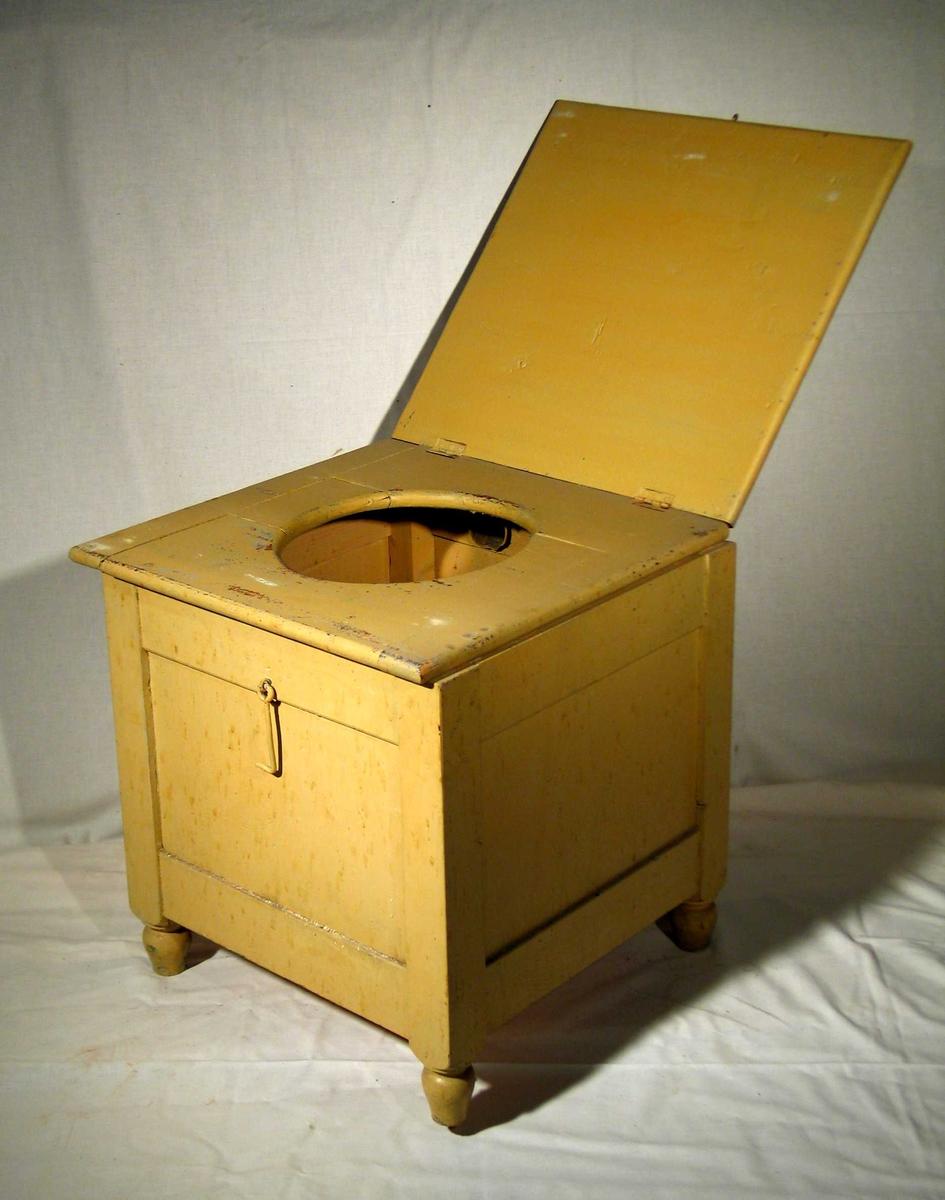 Gulmalt kasse i tre med hengslet lokk og sete. Dreide ben. Krok foran til lukking.