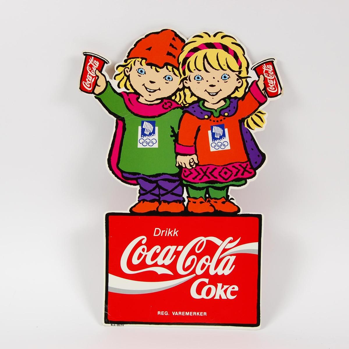 Reklameskilt med logo for Coca-Cola. Maskotene for de olympiske leker på Lillehammer i 1994, Kristin og Håkon, utgjør store deler av motivet og formen på skiltet. Skiltet er tosidig og likt på begge sider. Skiltet har noe slitasje.