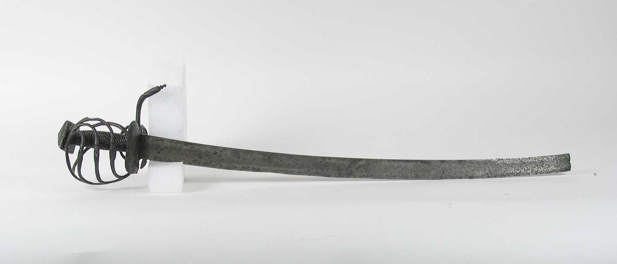 Pyramideformet knapp med strekdekor. Asymmetrisk kurvfeste med tre sidebøyler med riflede fortykkelser på midten mellom håndbøylen og kurvens ytterkant. Innsiden har en sidebøyle. Kurvens basis er en nyreformet parérplate  Tommelbøyle på innsiden. Opp og nedbøyde parérstenger med riflet dekor på endene. Fremre parérstang er avbrukket. Tregrep med nyere jerntrådvikling. Enegget krum klinge med ryggsliping og en bred hulslipning på ryggsiden, klingen er avbrukket.