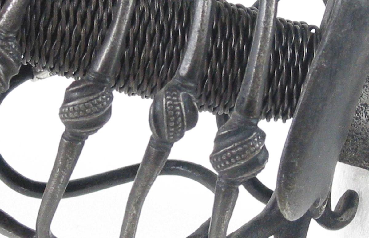 Pyramideformet knapp med kryssfilt dekor. Asymmetrisk feste med fire sidebøyler på utsiden med dekorerte fortykninger på midten. Innsiden har to sidebøyler, klingebrekker og  tommelbøyle. Rektangulær gjennombrutt og oppbøyet parérplate på utsiden. Svalt nedbøyde parérstenger med 8 kantet tverrsnitt og dråpeformede dekorerte fortykninger på endene. Tregrep med jernvikling. Enegget krum klinge med smedstemplel på venstre side. Klingen har bred hulslipning og gjeddenebb.