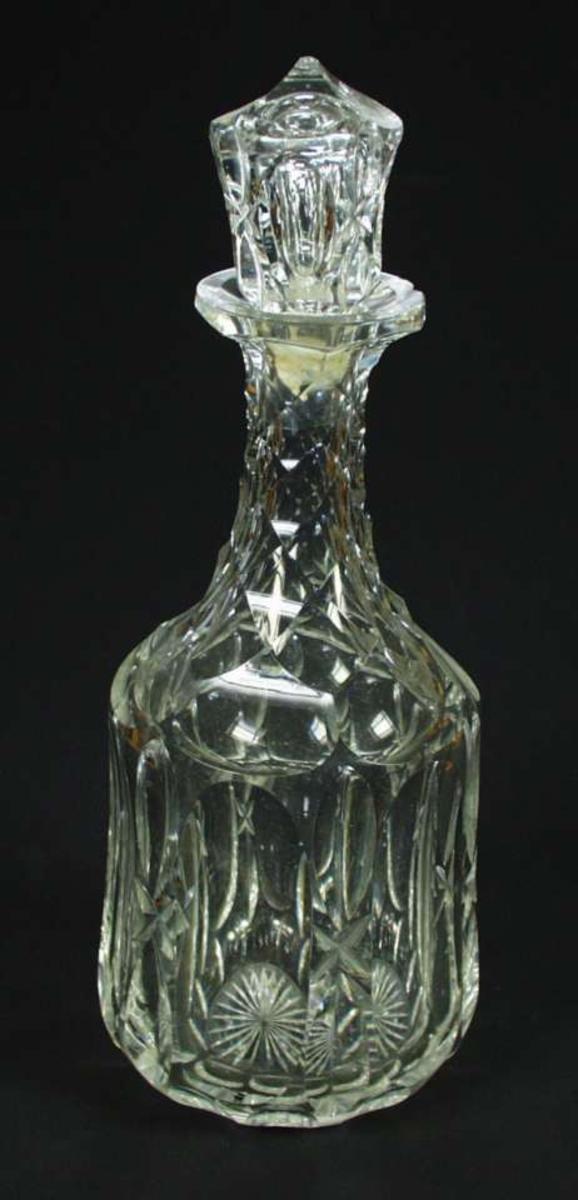 Klar karaffel av krystall med slipt dekor. Dekoren er skjærsliping og fasettsliping. Korken er knekt.