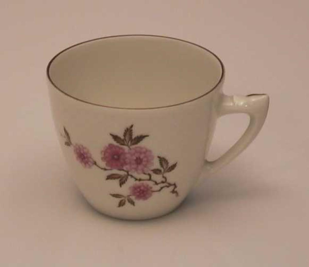 Kopp i porselen med blomsterdekor, gullkant og skjellmønster i godset.
