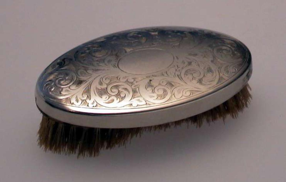 Oval børste med dekorert metallhode.