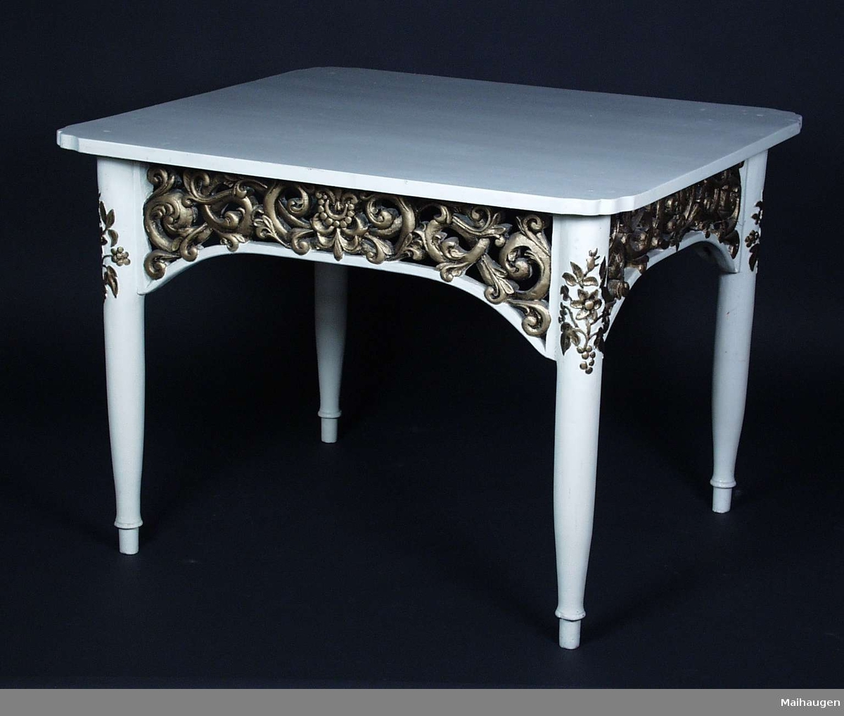 Hvitt bord i furu med akantus sarg. Øverst på bena er det blomster utskjæringer. Både akantus og blomserutskjæringene er malt med gull.