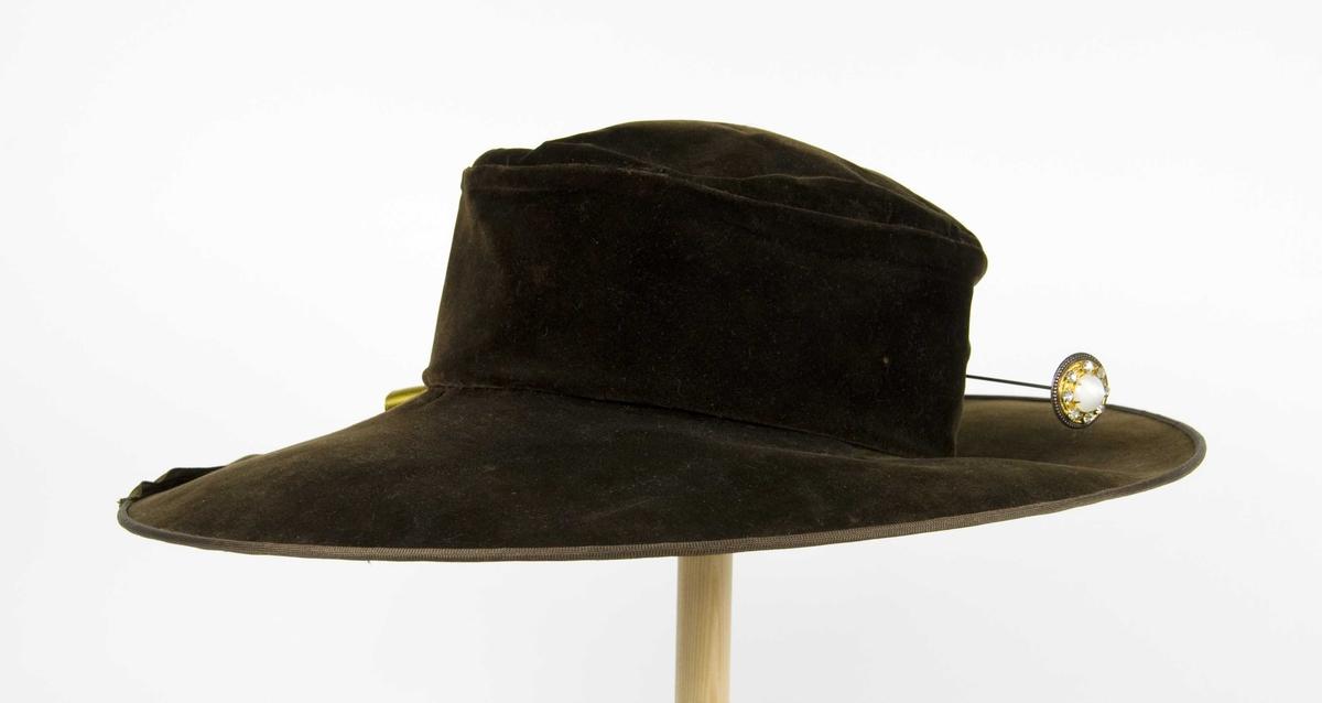 Grønn plysjhatt med høy pull og bred brem. hatten har et trefarget påsydd silkebånd som pynt på den ene siden (virker sekundær).  Midt bak en hattebnål. Fôr av silke.