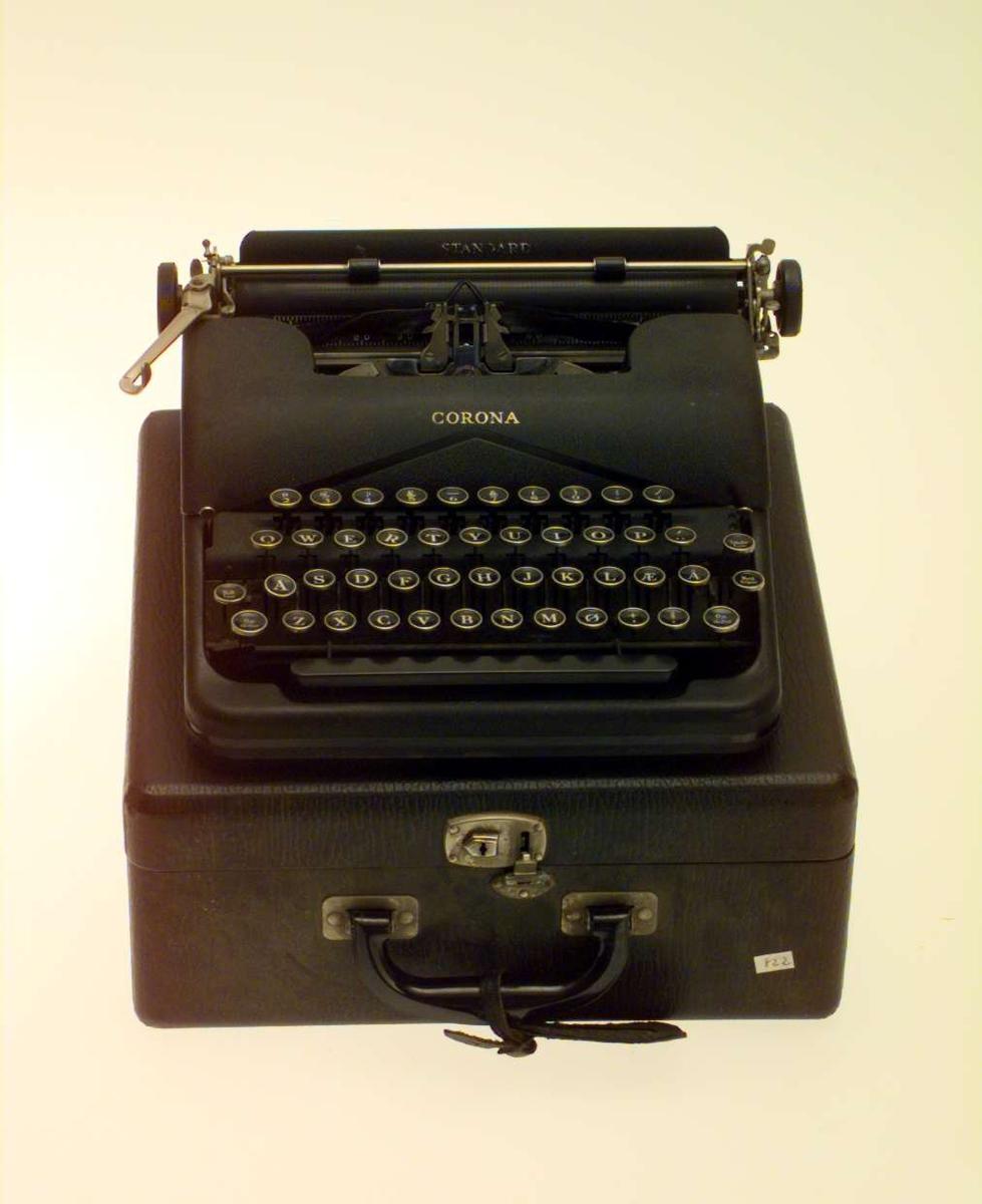 Sort reiseskrivemaskin med norsk tastatur. Skrivemaskinen har sort koffert med lås. I håndtaket henger en adresselapp med Sigrid Undsets navn, adressen er New York..