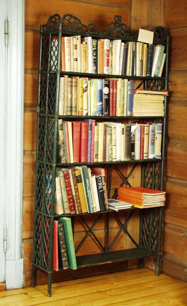 Grønnmalt bokreol med fem hyller. Hyllene er i heltre furu. Sidene og avstivningen i ryggen er grener/kvister i flettverk. Treslaget er ukjent. Bokreolen har en krone av flettverk som er formet som et ornament.