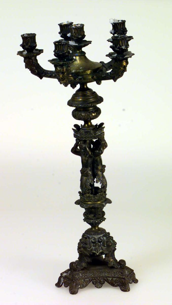 Stor kandelaber av bronsert bly og messing prydet med figurer og masker. Den står på trekantet fot. Den er 5-armet og har en sjette lysholder i midten. Staken er løs i de forskjellige sammenføyningene.