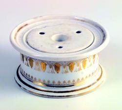 Blekkhus i keramikk. Farven er hvit med gylden dekor. Blekkhuset har rundt tverrsnitt. Det består av to deler. En bit er slått av kanten på blekkhuset