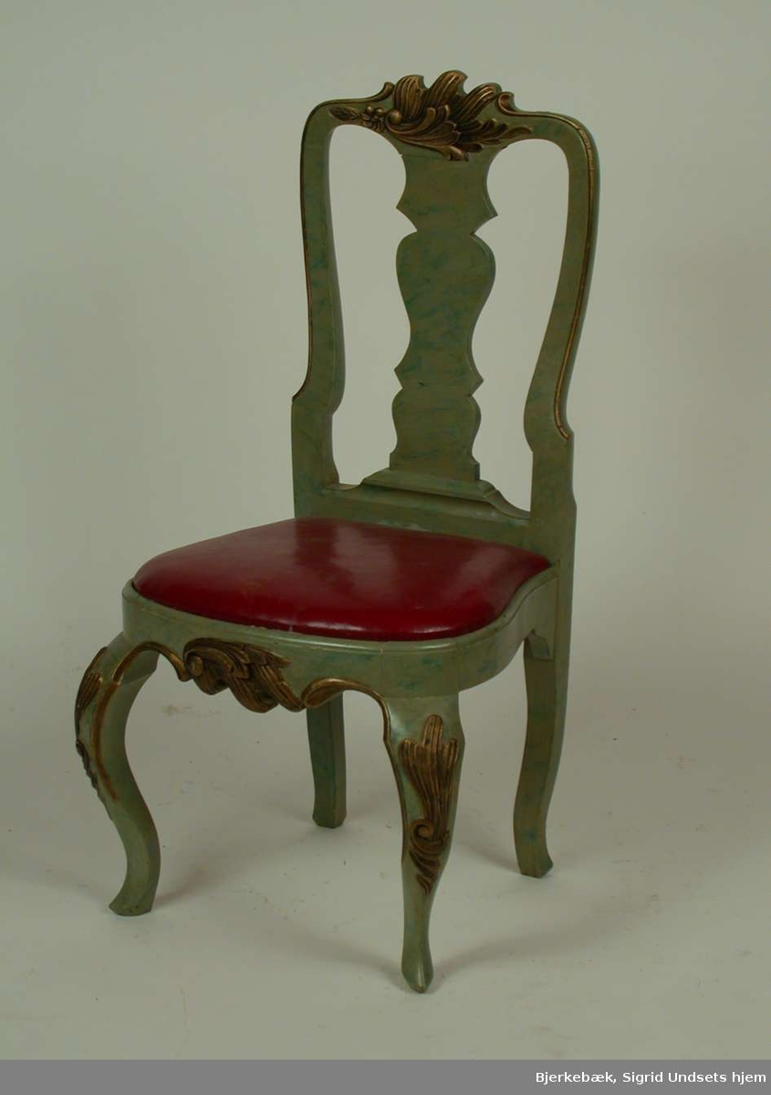 Lasert grønn stol med løst sete med polstring dekket med lær. Læret er rødt. Stolen har svungne forben med bronsert dekor på knærne. Stolen er dekorert med bronsert bladverk på sarg og toppstykke.